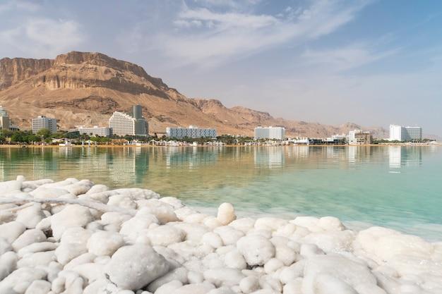 Vista della costa e degli hotel termali del mar morto, ein bokek, israele. formazioni di sale in primo piano. viaggia in israele. grandi cristalli di sale. giorno