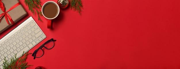 Sopra vista tazza di caffè, bicchieri e confezione regalo di natale su sfondo rosso.