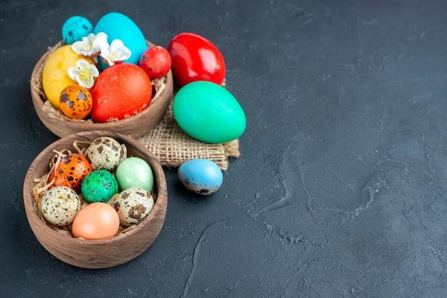 Sopra vista uova di pasqua colorate all'interno di piatti su superficie scura