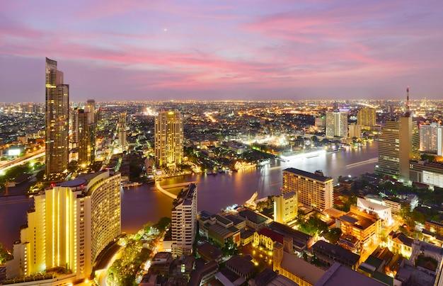 Osservi la costruzione moderna commerciale e il fiume chao phraya nella città del centro a tempo crepuscolare a bangkok, tailandia