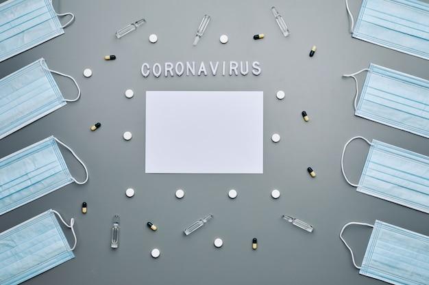 Vista sopra la composizione di maschere mediche che incorniciano carta bianca vuota con la parola coronavirus e farmaci disposti su sfondo grigio,