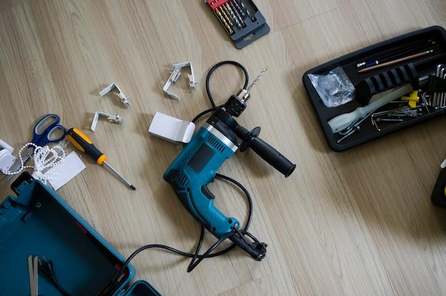 Sopra la vista del pavimento in legno di cacciavite a batteria e strumenti di costruzione.