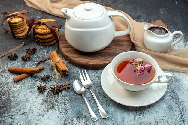 Sopra la vista di una tazza di tè nero e bollitore su tavola di legno biscotti impilati lime alla cannella su fondo di ghiaccio