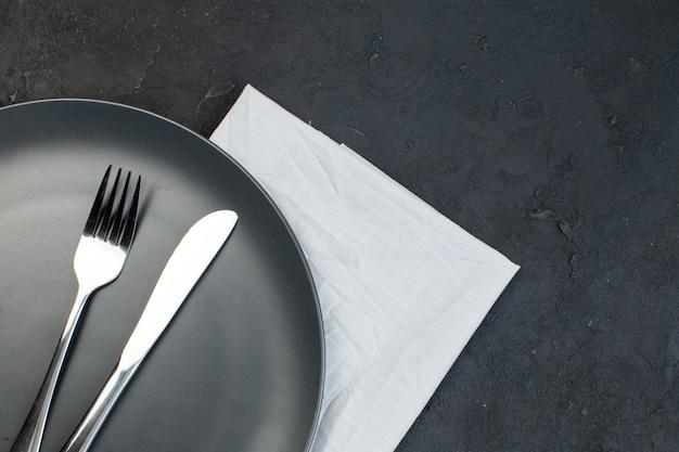 Sopra la vista delle posate su piastra nera su asciugamano bianco sul lato destro su sfondo di colore scuro con spazio libero