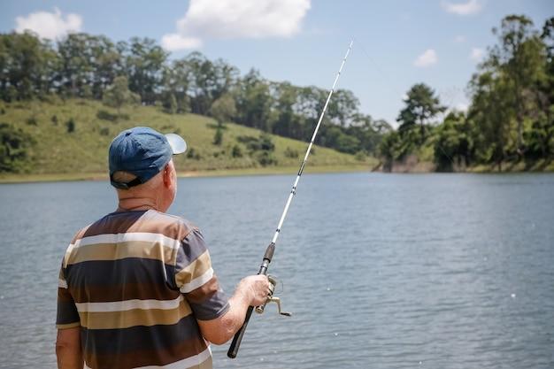 Visualizza la diga con il pescatore con un sacco di sole estivo brasiliano tropicale e nuoto per cani