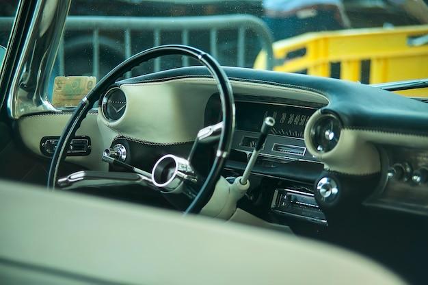 Vista del cruscotto, del volante, degli indicatori e degli indicatori di temporizzazione di un'auto americana d'epoca con tutti i dettagli degli interni visibili.
