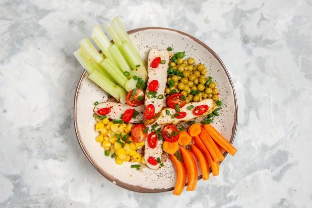Sopra la vista di una deliziosa insalata vegana su un piatto su una superficie bianca macchiata con spazio libero