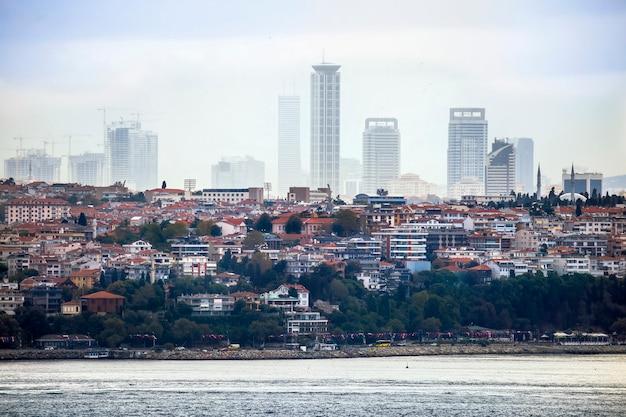 Vista di un quartiere con edifici residenziali e moderni di istanbul, lo stretto del bosforo in primo piano, turchia