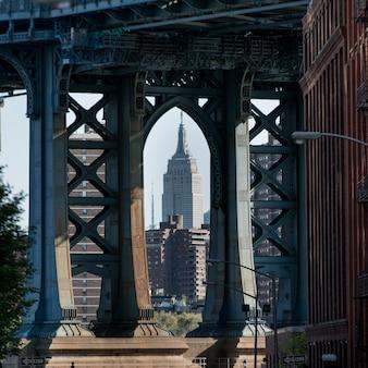 Vista dell'empire state building attraverso il ponte di manhattan, manhattan, new york, stato di new york