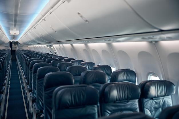 Vista dei sedili vuoti dell'aereo passeggeri nella cabina di colore blu