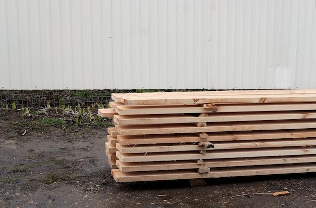 Vista delle estremità di tavole di larice con bordi impilati con bordo smussato, planken per la costruzione di recinzione o casa di rivestimento, legname preparato per la costruzione