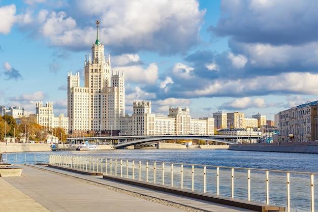 Vista del famoso grattacielo di stalin sull'argine di kotelnicheskaya contro il molo delle navi da crociera sul fiume moskva nella soleggiata giornata autunnale
