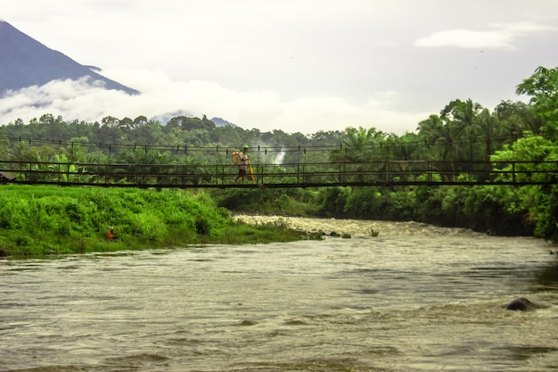 Una vista di un contadino che cammina su un ponte sospeso su un fiume veloce nel nord bengkulu, indonesia