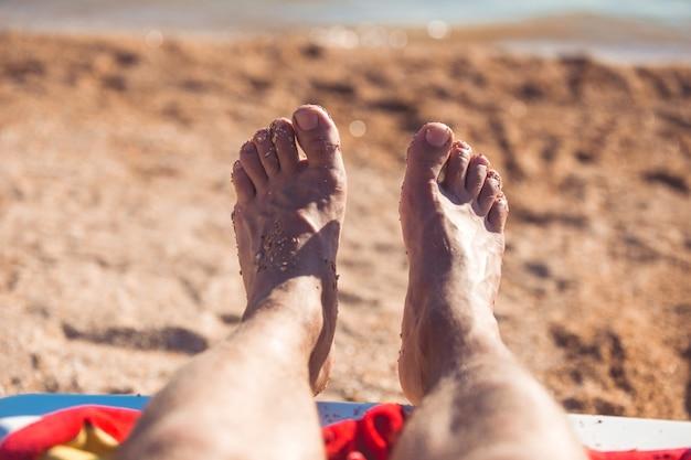 Vista dei piedi dell'uomo che sono coperti di sabbia su una spiaggia.