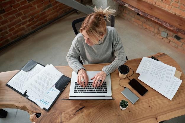 Sopra la vista del manager femminile in maglione che digita sul laptop durante l'analisi dei documenti in ufficio