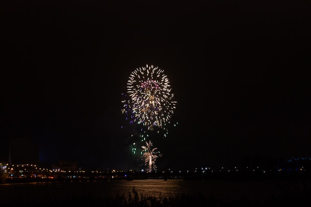 Visualizza fuochi d'artificio sullo sfondo notte oscura sopra la città. concetto di vacanza e divertimento