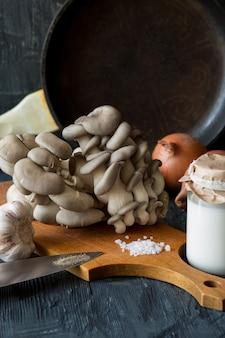 Vista di funghi ostrica fresca con panna, spezie, erbe aromatiche e verdure su fondo di legno scuro.