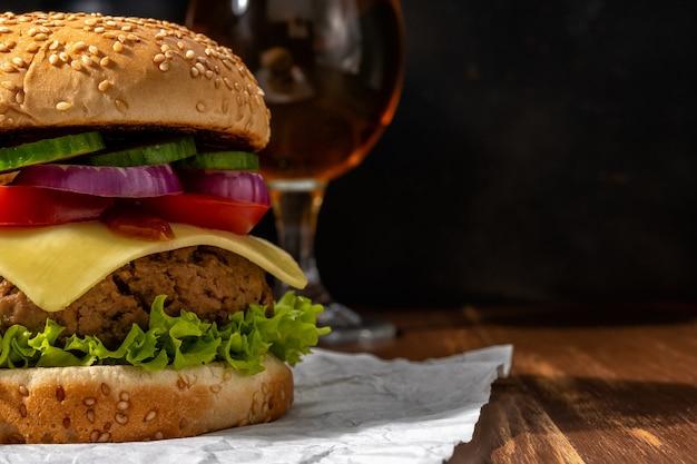 Vista del gustoso hamburger fresco con un bicchiere di birra sulla tavola rustica in legno.