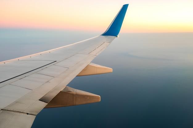 Vista dall'aereo sull'ala bianca degli aerei che sorvola il paesaggio dell'oceano nella mattina soleggiata. concetto di trasporto aereo e di trasporto.