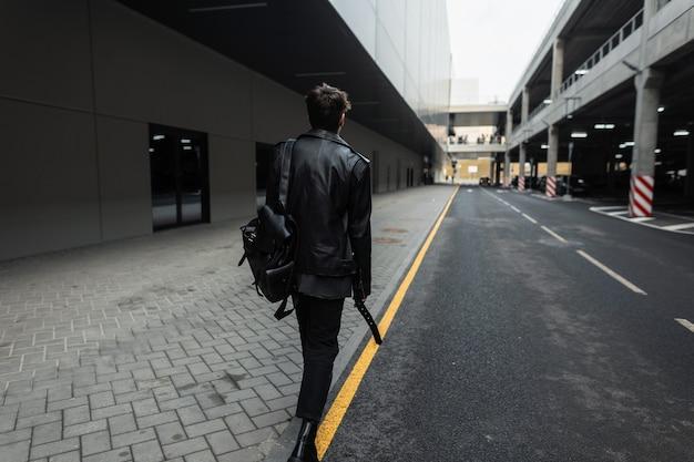 Vista dal retro di un giovane alla moda con l'acconciatura alla moda in giacca di pelle nera oversize in jeans in stivali alla moda con uno zaino per strada in città. ragazzo alla moda in abbigliamento casual giovanile