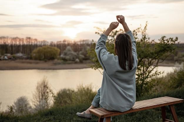 La vista dalla schiena della ragazza guarda il tramonto, seduta su una panchina
