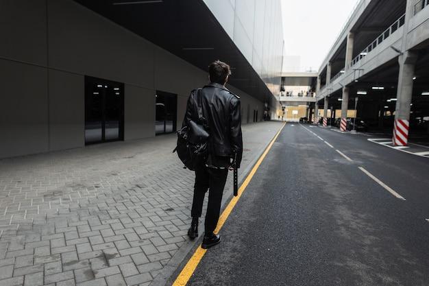 Vista dal retro del giovane moderno con l'acconciatura in giacca di pelle nera oversize alla moda in jeans in stivali primaverili con uno zaino per strada in città. ragazzo in elegante abbigliamento casual giovanile