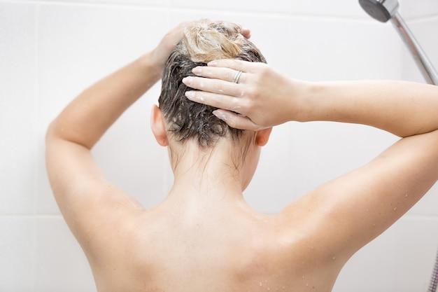 Vista dal retro di una donna sexy che lava i capelli con lo shampoo