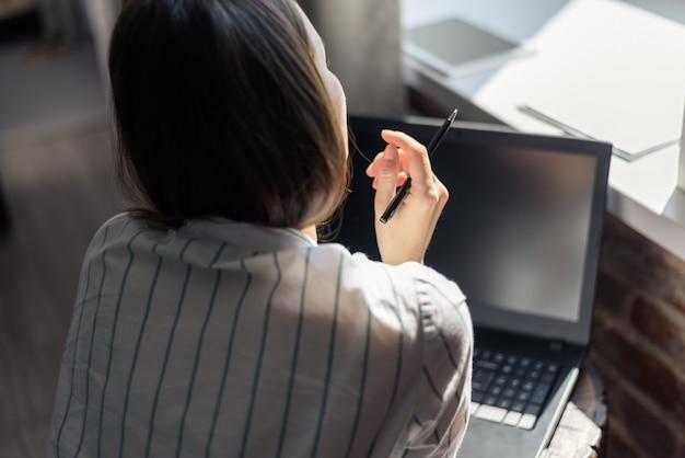 Vista da dietro, una donna davanti a un computer portatile al tavolo, guardando fuori dalla finestra, lavoro a distanza, indipendente