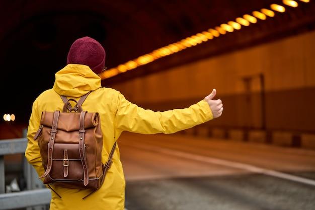 Vista dal retro del giovane che fa l'autostop per il paese, cercando di catturare un'auto di passaggio