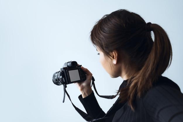 Vista dal retro una giovane donna scatta fotografie con una moderna fotocamera digitale