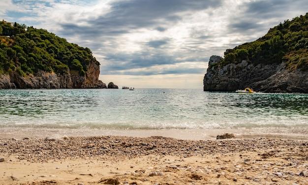 Vista dalla spiaggia di una splendida baia con acqua cristallina a paleokastritsa sull'isola di corfù, grecia. bellissimo paesaggio di due rocce con alberi.