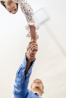 Vista dal basso di un uomo d'affari e di una donna che stringono la mano concettuale di un accordo o di una partnership con lo spazio della copia su un soffitto bianco.