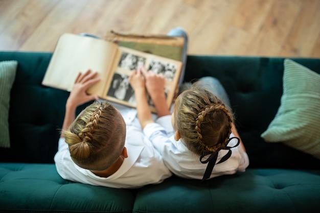 Vista dall'alto. bambini ragazzo e ragazza seduti su un divano verde e guardando un vecchio album con le foto