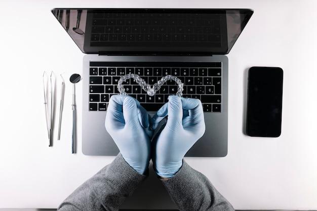 Vista dall'alto delle mani del medico con allineatori dentali a forma di cuore