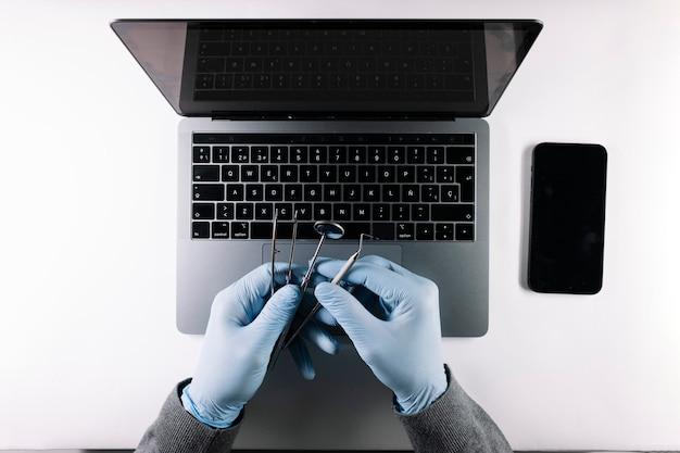 Vista dall'alto delle mani del medico con i suoi strumenti di lavoro e laptop grigio