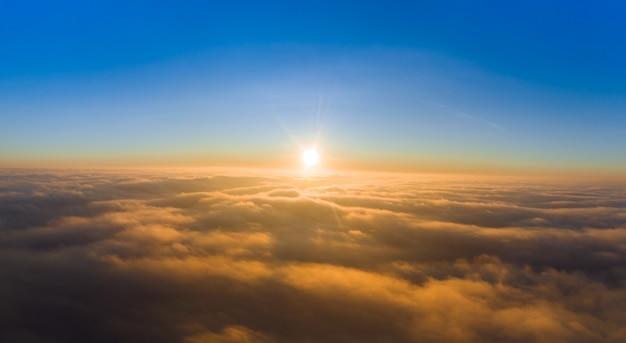 Vista dal drone all'alba sopra le nuvole con le montagne sulla prateria.