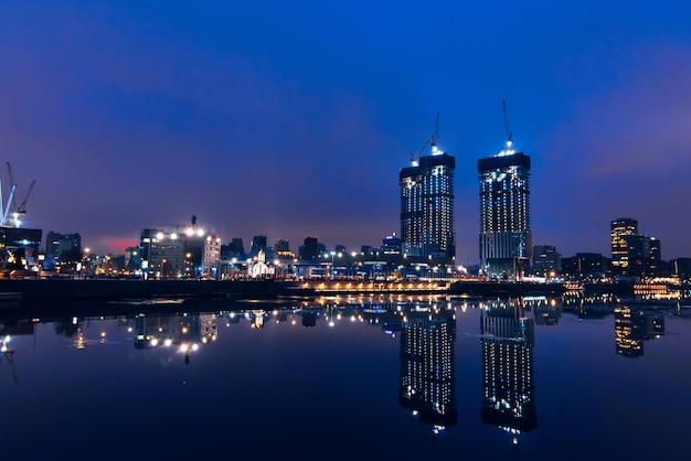 Vista dall'argine di alti grattacieli riflessi nell'acqua