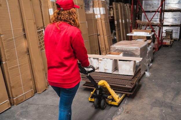 Una vista da dietro di una lavoratrice con un transpallet in un magazzino