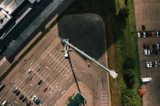 Vista dall'alto dell'auto gru pesante che è aperta nel parcheggio e pronta a lavorare. la gru per autocarro più alta è installata sul sito. l'altezza del boma è di 80 metri.