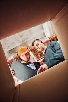 Vista dall'interno della scatola. due persone con blocco note hanno un lavoro.