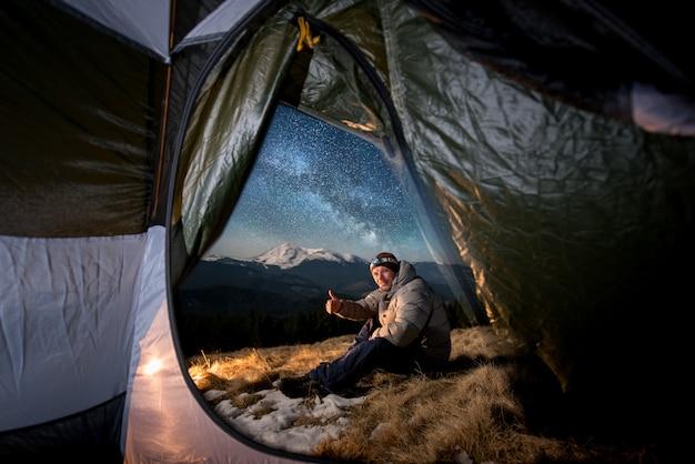 Vista dall'interno di una tenda sul turista maschio riposarsi nel suo campeggio in montagna di notte. uomo seduto vicino al fuoco, guardando la telecamera e mostrando il pollice in alto sotto il cielo stellato e la via lattea