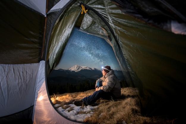 Vista dall'interno di una tenda sul turista maschio riposarsi nel suo campeggio in montagna di notte. uomo con un faro seduto vicino al fuoco sotto un bel cielo notturno pieno di stelle e via lattea