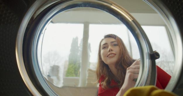 Vista dall'interno lavatrice sulla bella donna felice caucasica aprendo e tirando fuori i vestiti lavati puliti. chiuda in su della ragazza allegra affascinante in una lavanderia automatica pubblica