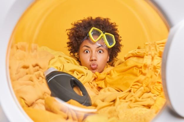 Vista dall'interno della lavatrice piena di biancheria. donna riccia divertente con maschera da snorkeling sulla fronte