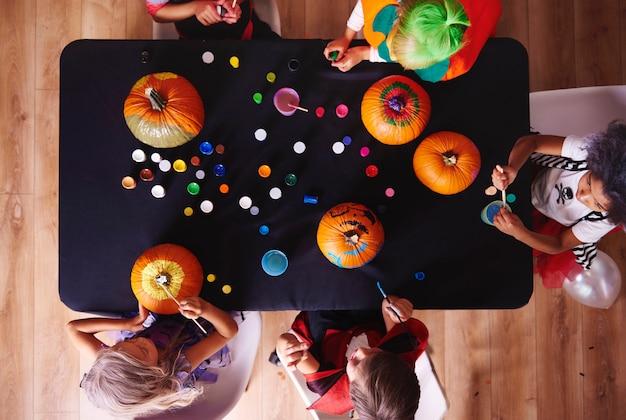 Vista dall'alto bambini che dipingono zucche