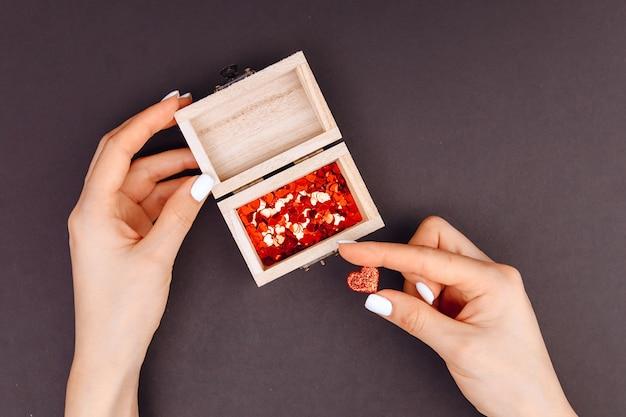 Vista dall'alto. le mani della signora tengono un piccolo cuore rosso, accanto a una scatola con dentro i cuori. concetto di san valentino. scatola di legno. 14 febbraio 2021