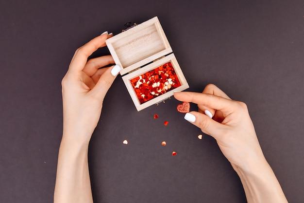 Vista dall'alto. le mani della signora tengono un piccolo cuore rosso, accanto a una scatola con dentro i cuori. concetto di san valentino. scatola di legno.