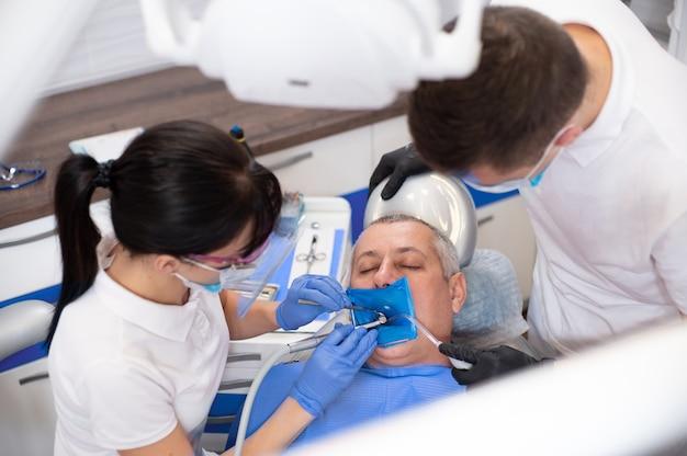 Vista dall'alto al paziente seduto su una poltrona odontoiatrica. dentisti che trattano il dente