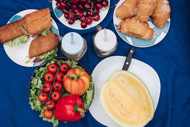 Vista dall'alto di piatti con verdure fresche sane, ciliegie rosse, melone succoso, deliziosi panini con pollo, croissant al cioccolato e bevande. concetto di picnic e prodotti.
