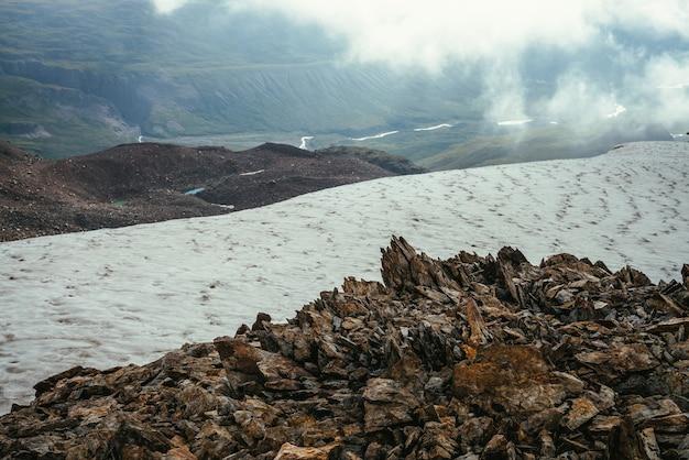 Vista dal bordo del precipizio con rocce taglienti e cornice di neve alla valle di montagna in nuvole basse. meraviglioso scenario di montagna con nuvole basse nella valle dell'altopiano. paesaggio alpino scenico con montagne rocciose